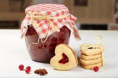 Hart gevormde koekjes en kruik jam Stock Fotografie
