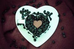 Hart gevormde kop met koffiebonen op bruin royalty-vrije stock afbeelding
