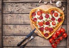 Hart gevormde pizza met pepperonis, tomaten en stock foto's