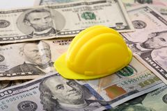 Hart Hat On Dollar Banknotes. Close-up Of Yellow Hard Hat On Dollar Banknotes royalty free stock photo