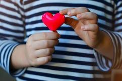 Hart in kind` s handen Stock Afbeelding