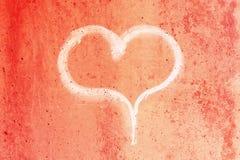 Hart in krijt op een rode concrete muur wordt getrokken die royalty-vrije stock foto