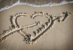 Hart met een pijl op het zand wordt getrokken dat Stock Foto's