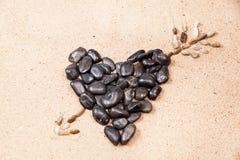 Hart met kiezelstenen op het strandzand dat wordt getrokken Royalty-vrije Stock Foto's