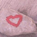 Hart met lippenstift op stuk van steen wordt geschilderd die stock fotografie