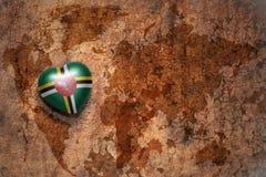 Hart met nationale vlag van dominica op een uitstekende de barstdocument van de wereldkaart achtergrond Stock Foto's