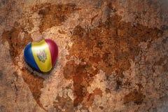 Hart met nationale vlag van moldova op een uitstekende de barstdocument van de wereldkaart achtergrond royalty-vrije stock afbeeldingen