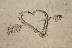 Hart met pijl die in zand wordt geschreven stock afbeeldingen