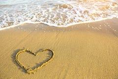 Hart op het zand van een overzees strand wordt getrokken dat Royalty-vrije Stock Foto's