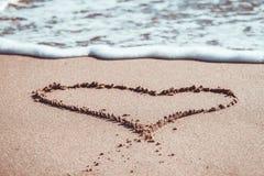 Hart op het zand van het strand en de blauwe overzeese golven met schuim wordt getrokken dat Royalty-vrije Stock Afbeelding