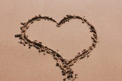 Hart op overzees zand in een Zonnige de zomerdag die wordt geschreven stock foto