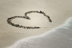 Hart op zand met golf het naderbij komen stock afbeelding