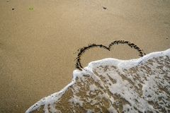 Hart in sand washed by waves. In in different stages Royalty Free Stock Photo