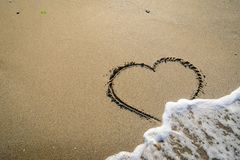 Hart in sand washed by waves. In in different stages Stock Image