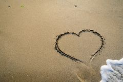 Hart in sand washed by waves. In in different stages Stock Photos
