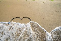 Hart in sand washed by waves. In in different stages Royalty Free Stock Photography