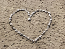 Hart shape made by bright stones on the sand Stock Photos