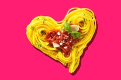Hart-shaped pasta on pink background. Decorative heart-shaped Italian pasta portion, formed of cooked spaghetti, topped with tomatoes, basil, and parmesan cheese stock image