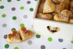 Hart twee vormde koekjes met sesam op keukenhanddoek met punten en decoratief houten dozenhoogtepunt van het stock afbeeldingen