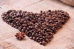 Hart uit koffiebonen wordt gemaakt op weefselachtergrond die Stock Foto