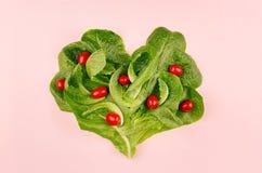 Hart van de lente gezond voedsel - van kersentomaten en bladeren spinazie op roze achtergrond De dagachtergrond van Valentine ` s Stock Foto