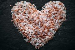 Hart van Himalayan-zout op zwarte lei wordt gemaakt die Hoogste mening Hart gevormd zout als achtergrond royalty-vrije stock afbeeldingen