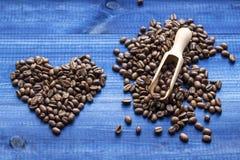 Hart van koffiebonen wordt gemaakt met houten lepel op blauwe houten achtergrond die Stock Afbeeldingen