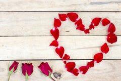 Hart van rode bloemblaadjes dat op houten wordt gemaakt Stock Fotografie