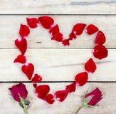 Hart van rode bloemblaadjes dat op houten wordt gemaakt Stock Afbeelding