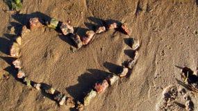 Hart van roodachtige stenen op de zandige kust stock foto's