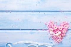 Hart van roze bloemen en bloemblaadjes op blauwe houten planken wordt gemaakt die Royalty-vrije Stock Afbeeldingen