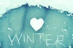 Hart van sneeuw en de woordwinter op ijs wordt gekrast dat Het thema van de winter royalty-vrije stock afbeelding