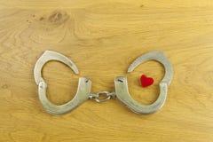 Hart verbindend door liefde, politiehandcuffs en hart Stock Afbeeldingen