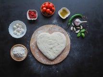 Hart-vormig deeg en een reeks ingrediënten voor pizza op een zwarte lijst De mening vanaf de bovenkant stock foto