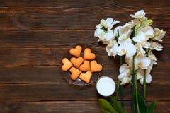 Hart-vormige koekjes, melk en orchidee op een donkere houten backgroun Stock Afbeelding