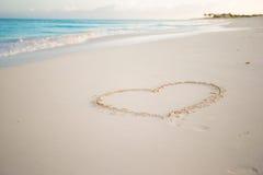 Hart in wit zand op een tropisch strand wordt geschilderd dat Stock Foto