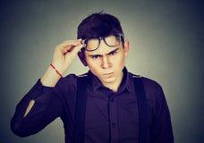 Hart- - zum bitte jungen Mann, der skeptisch Kamera betrachtet lizenzfreie stockfotografie