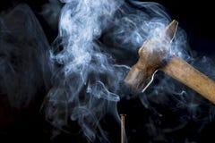 Harte Arbeits-Konzept Abstraktes Foto des Metallrostigen Hammers über Nagel mit Rauche auf schwarzem Hintergrund Stockfoto