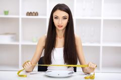 Harte Diät - verbotenes Essen Mädchen hält eine Platte und versucht, eine Erbse zu setzen lizenzfreie stockfotografie