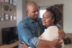 Hartelijk Afrikaans paar die elkaar thuis koesteren royalty-vrije stock foto