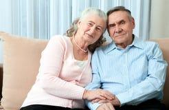 Hartelijk bejaard paar met mooie richtende vriendschappelijke glimlachen die samen in een dichte greep in hun woonkamer stellen P royalty-vrije stock fotografie