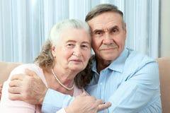 Hartelijk bejaard paar met mooie richtende vriendschappelijke glimlachen die samen in een dichte greep in hun woonkamer stellen P stock afbeeldingen