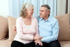 Hartelijk bejaard paar met mooie richtende vriendschappelijke glimlachen die samen in een dichte greep in hun woonkamer stellen P royalty-vrije stock afbeeldingen