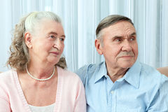Hartelijk bejaard paar met mooie richtende vriendschappelijke glimlachen die samen in een dichte greep in hun woonkamer stellen P stock fotografie