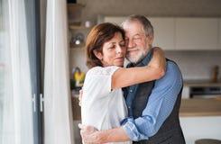 Hartelijk hoger paar in liefde die binnen, het koesteren zich thuis bevinden royalty-vrije stock afbeeldingen