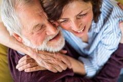 Hartelijk hoger paar in liefdezitting op bank binnen thuis, het koesteren royalty-vrije stock foto