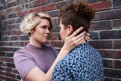 Hartelijk jong lesbisch paar die elkaar buiten onderzoeken de ogen van ` s royalty-vrije stock afbeelding