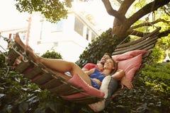 Hartelijk jong paar die op tuinhangmat liggen royalty-vrije stock foto