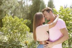Hartelijk jong paar ongeveer aan kus in park royalty-vrije stock afbeelding