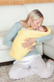 Hartelijk mamma dat haar baby kust die in een dekking verpakt is stock afbeeldingen